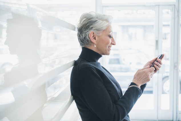 Mature woman with short grey hair texting on cell phone in modern office. Female professional using mobile phone at work, smiling.